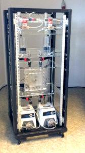 De testopstelling met in de midden de transparante elektrolyse-cel